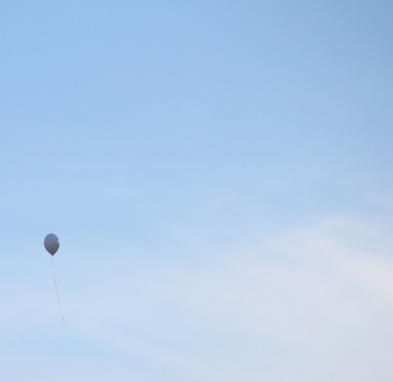 A single balloon floats into the sky