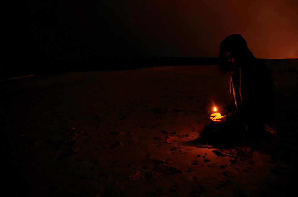 Holding a candle on the beach