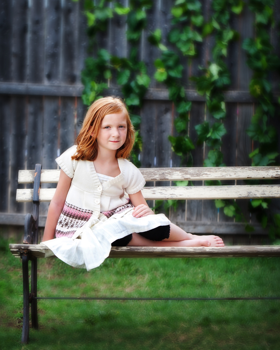 Redheaded girl sitting on a bench